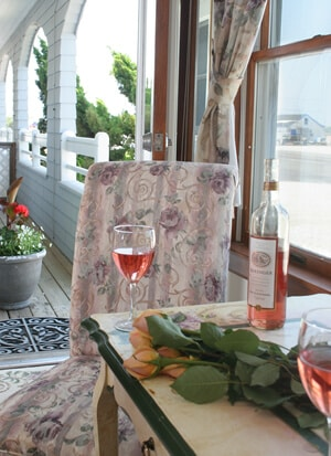 Sunroom and patio, flowers on table with wine and glass.