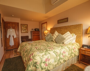 Room showing king bed with woven sea grass headboard and tropical colors and mini-fridge, microwave and mounted flat screen television