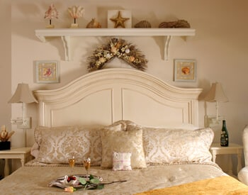 Room showing off-white king headboard with seashore décor and champagne and chocolate covered strawberries