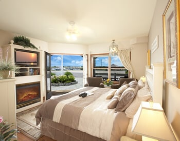 Room showing king bed, fireplace, television, two brown chairs and panoramic view of the bay water.