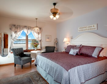 Room overview showing king bed with white headboard and lavender accents with large window showing boats and bay view.