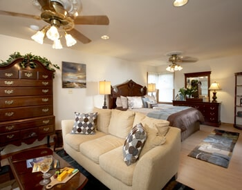Suite showing overview of living area couch and cherry king bed and dresser with beige, blue and brown accent colors.