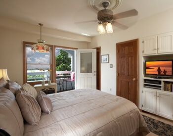 Room showing king bed, television and DVD player with outdoor entrance from private porch overlooking the blue bay water