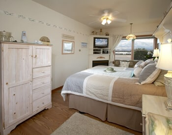 Seascapes Room with whitewashed armoire large bed with muted color-block quilt.