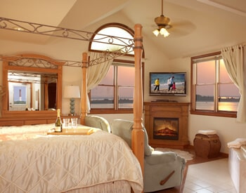 Suite showing king four poster bed, two blue recliner chairs and large Jacuzzi with windows overlooking sunset on the bay