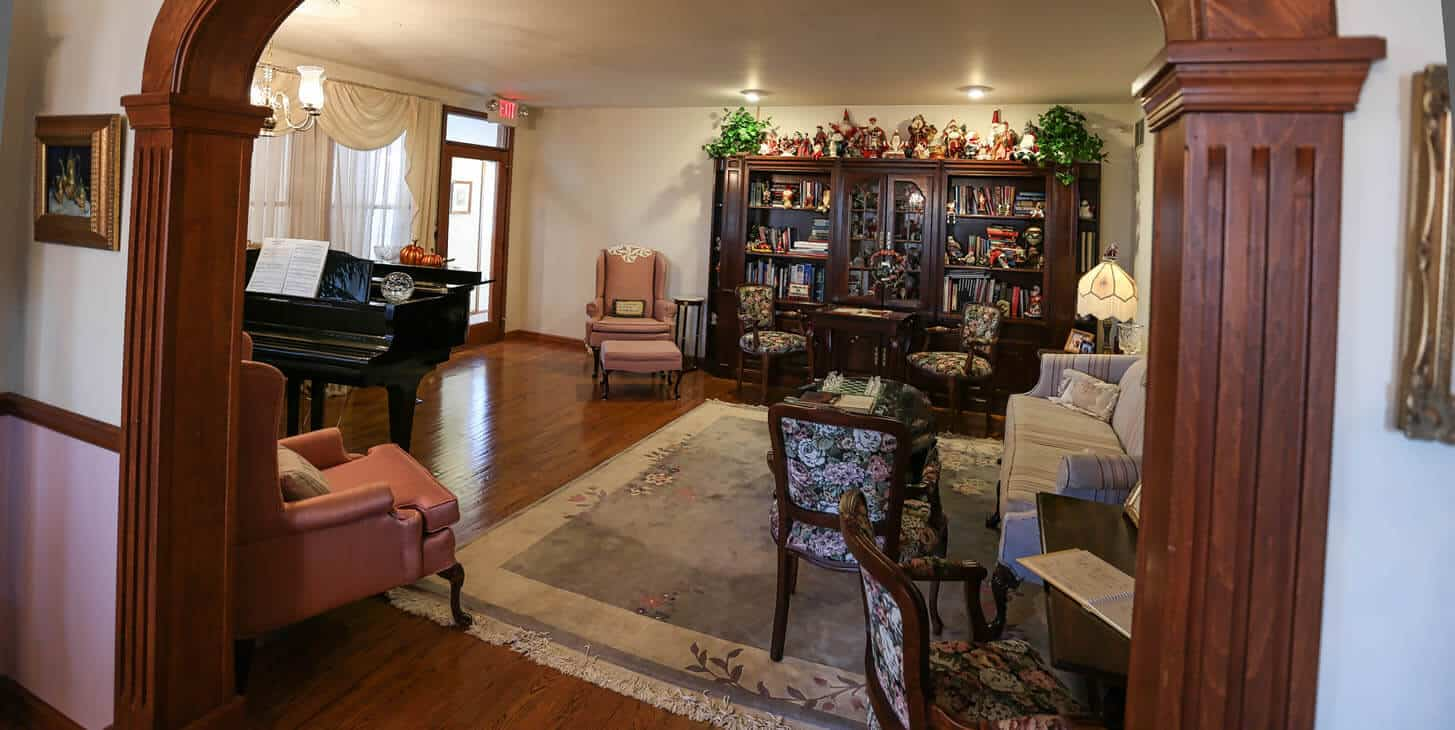 Parlor showing ebony grand piano, game tables and Santa Claus collection with comfortable couch and chairs.