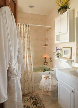 Bathroom showing romantic tub setting with white plush robe and soft towels.