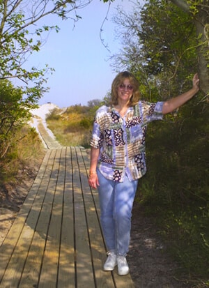 Innkeeper standing at entrance of the wooden walkway through the sand dunes nature trail.