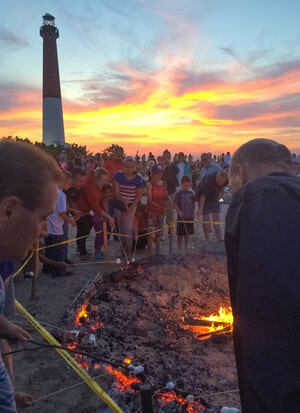 Crowd of people standing around a bonfire roasting marshmallows with sky lit by colorful sunset and lighthouse in background.