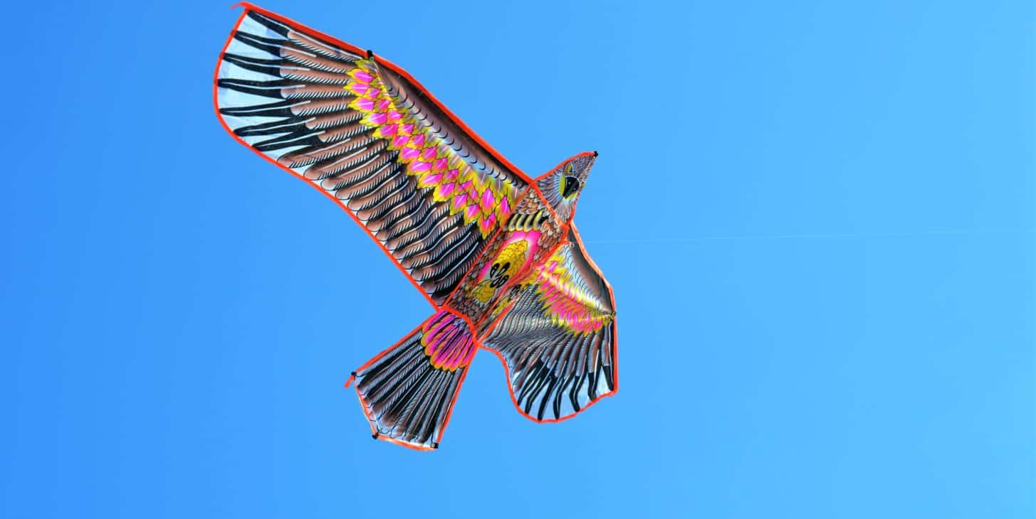 artistic bright colored kite shaped like an eagle soaring through the blue skies