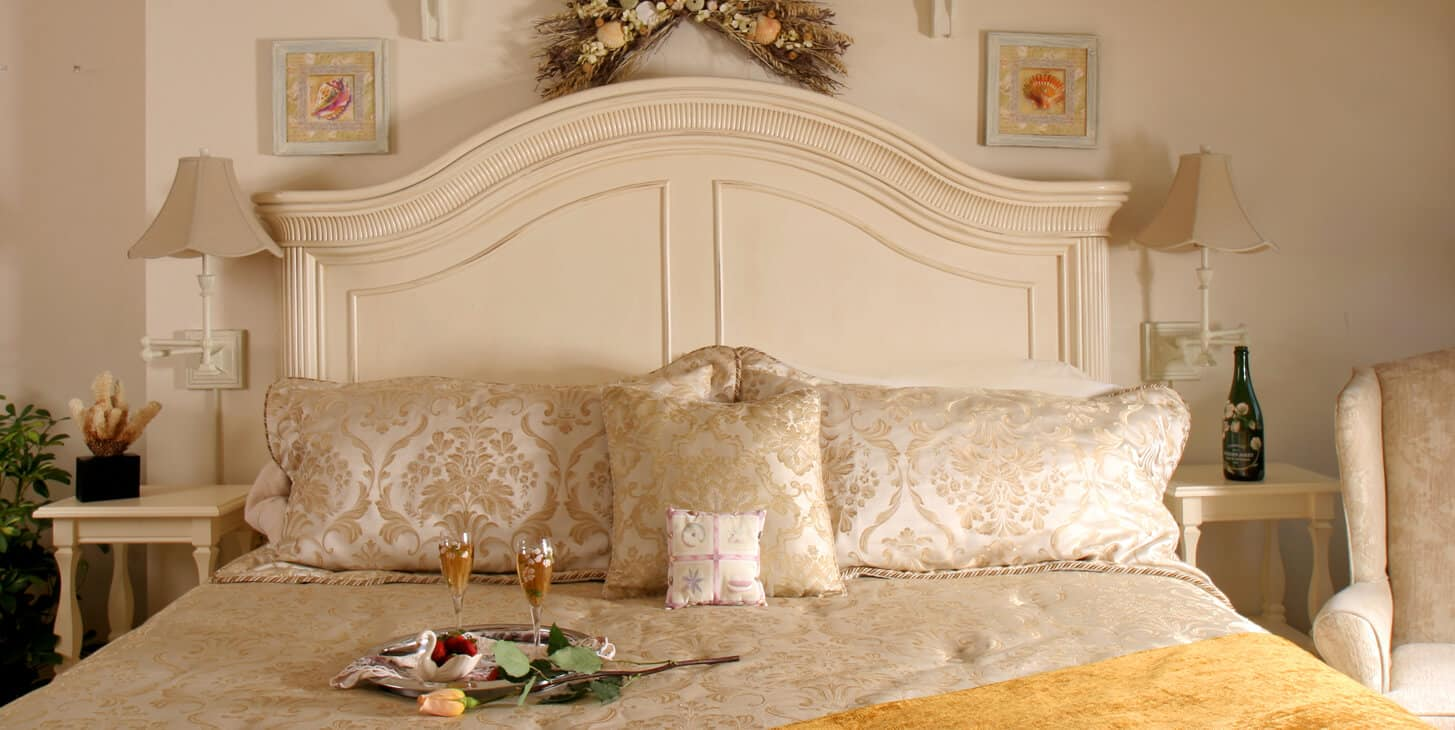 Room showing off-white king headboard with seashore décor and champagne and chocolate covered strawberries.