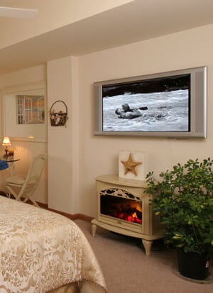 Beige guest room, carpeted, with fire stove and flat screen TV