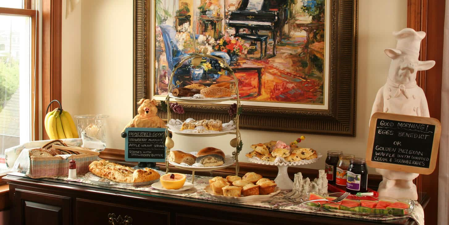 Breakfast buffet on sideboard. Pasties and fruit mainly. 2 ceramic pigs holding blackboard menus--one large, one small
