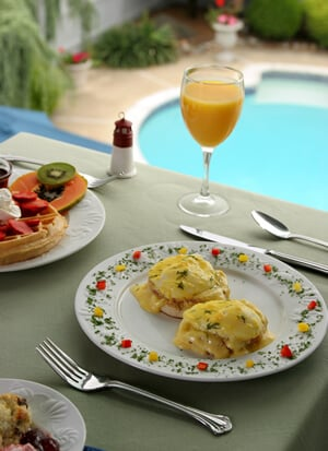 Table on the sun porch overlooking the pool showing breakfast of eggs benedict on a colorfully decorated plate.