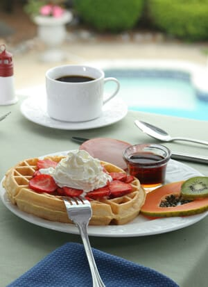 Breakfast table showing golden Belgian waffle topped with whipped cream.