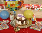 Decorated cake in front of happy birthday balloon and banner. Balloons, hat, colorful napkins on table.