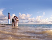 Couple in street clothes strolling in tide, gazing at each other. Lighthouse, sky with puffy clouds, ocean in background.