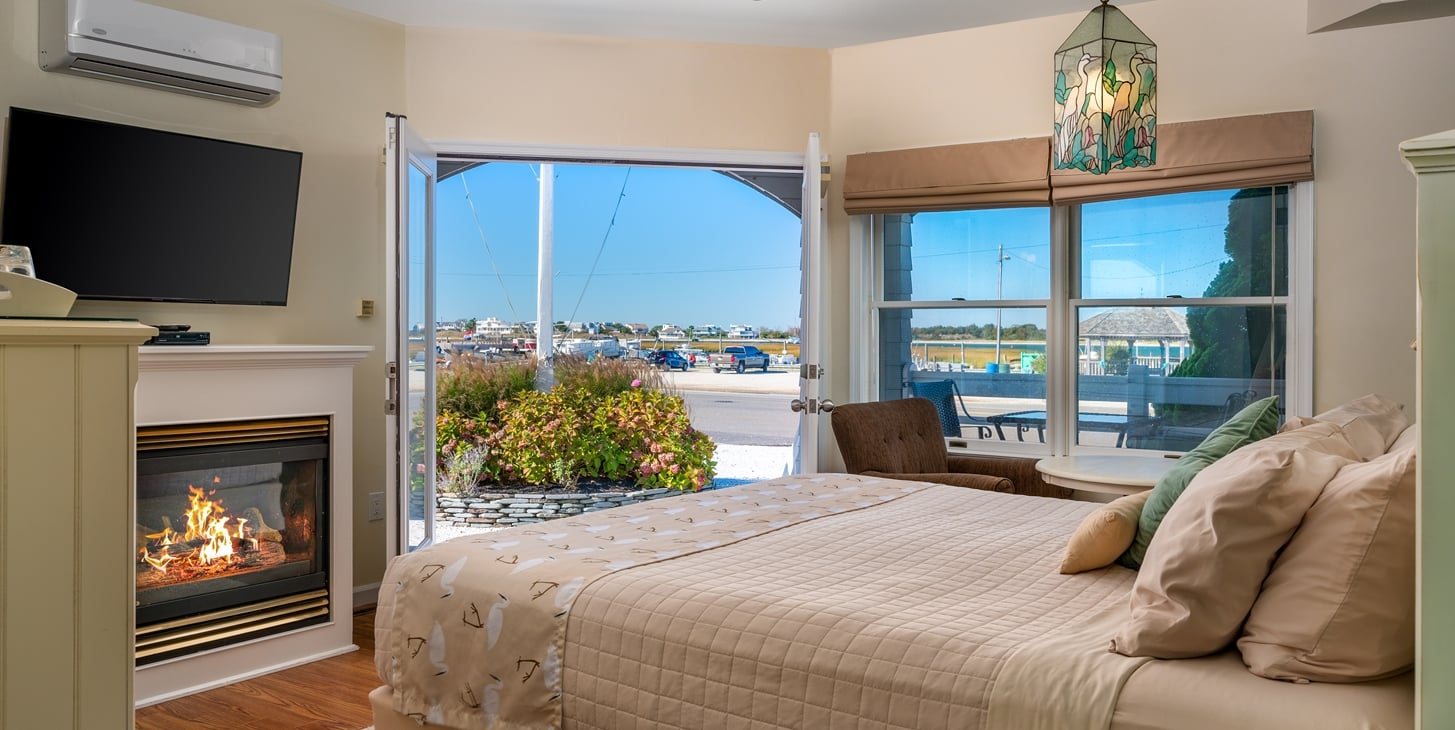 Room showing king bed, fireplace, television, two brown chairs and panoramic view of the bay waters.