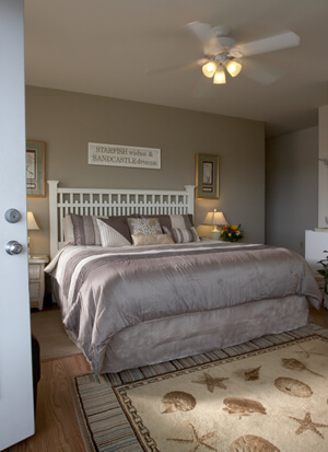 Room view from private exterior entrance showing king bed with white picket fence headboard and taupe colors.
