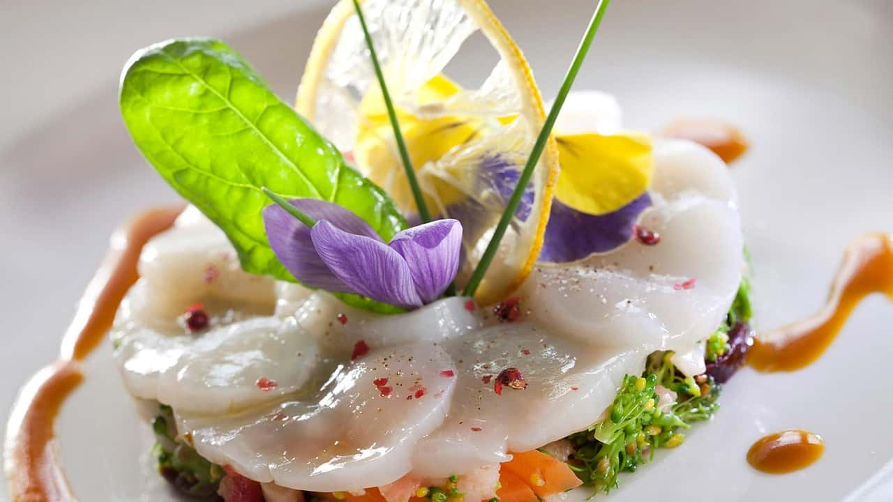Beautiful gourmet seafood dish topped with flower petals, a leaf, lemon slice and chive sprigs
