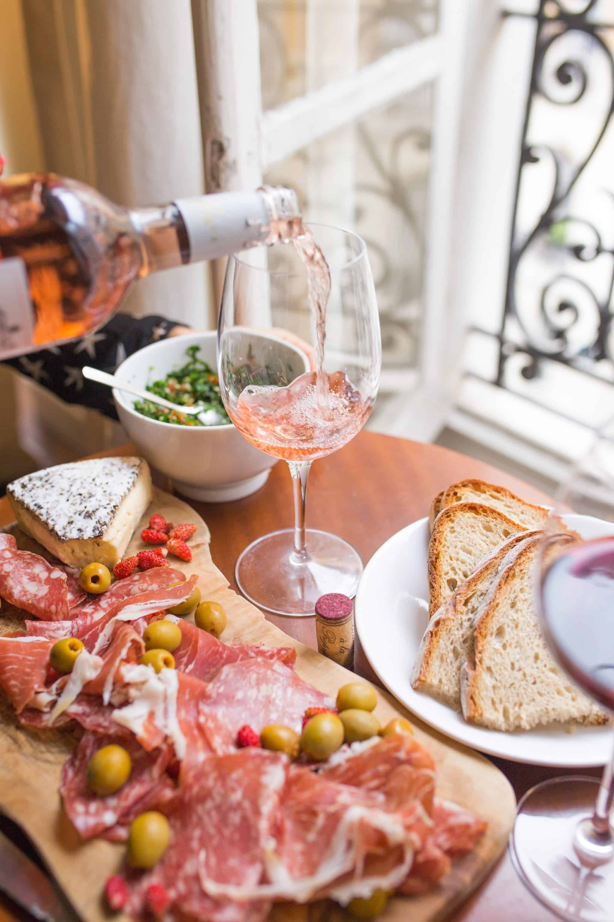 Dining table topped with bread prosciutto, cheese, salad and rosé wine