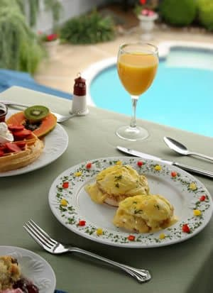 Breakfast. Floral plate with eggs benedict. Partial view of other plates, different food. Orange juice.  Pool visible in background, below.
