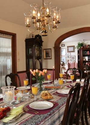 Dining room. Table with OJ at each setting.  Baked goods, fruit. 5 dark wood chairs visible., chandelier. Looking into parlor.