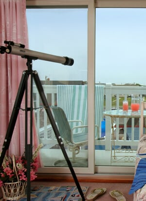 Inside room with telescope looking out over patio. Punch on patio table.