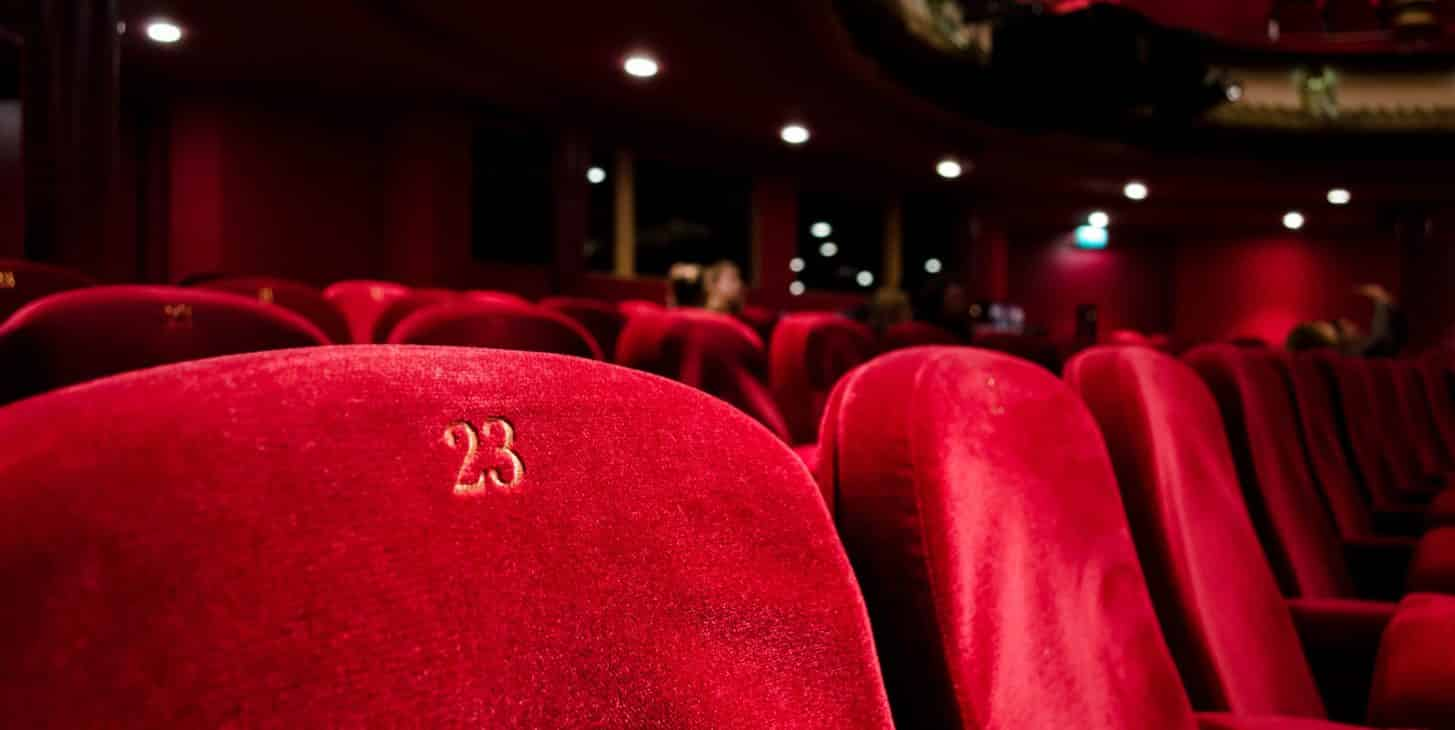 Rows of red velvet seats in a dark theatre