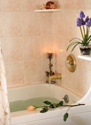 Bathroom showing Jacuzzi tub filling with water and peach colored tile walls