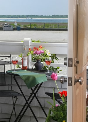 Entrance to room showing outside porch with bistro table and chairs overlooking a sailboat on the blue bay waters