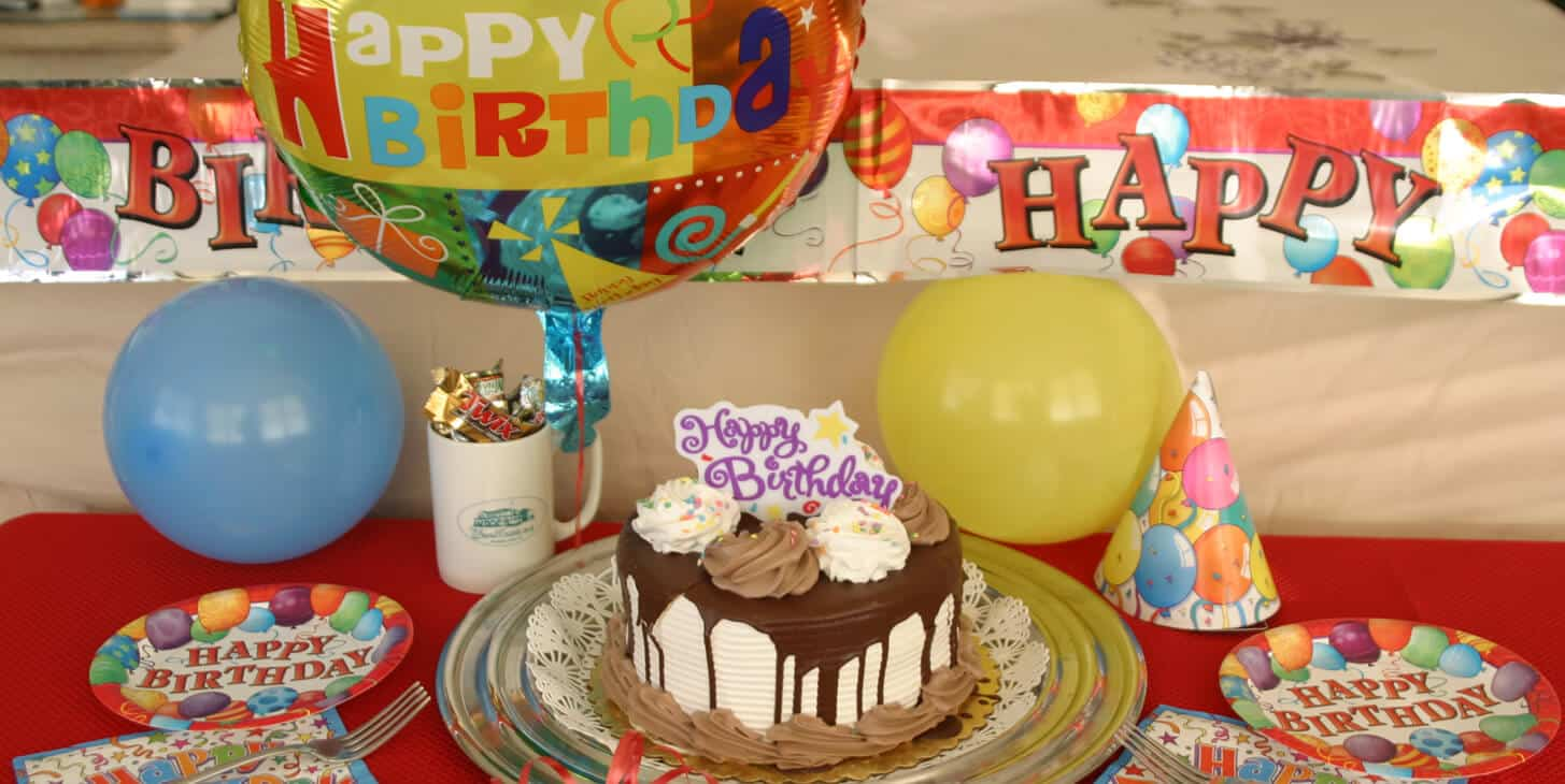 Decorated birthday cake with colorful helium balloons, banner, birthday plates and napkins and a mug of candy.