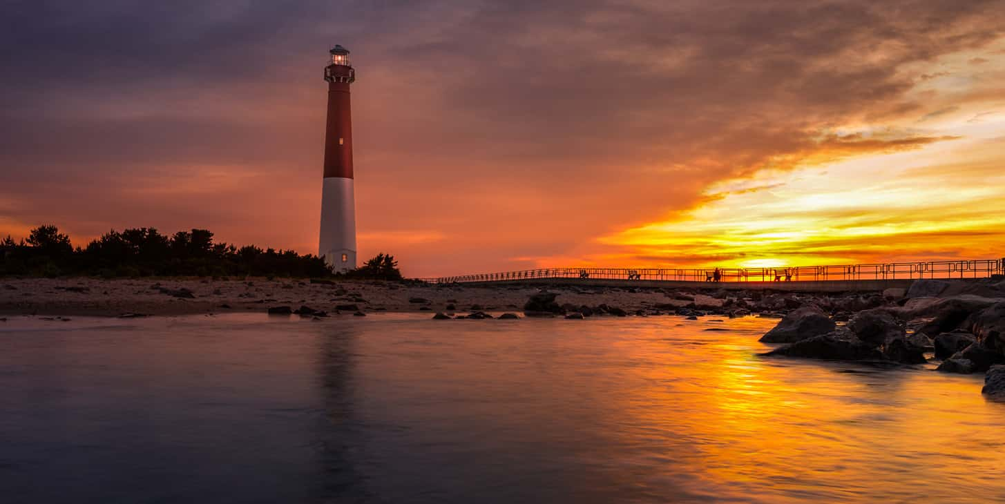 Red and white Barnegat Lighthouse with reflection in the bay water and rock jetty