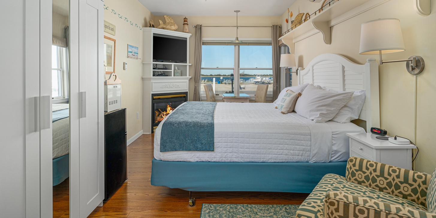 Room showing king bed, fireplace, flatscreen TV and large window overlooking the blue water of the bay.