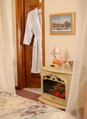 Inside room, fireplace stove (electric?) operating. White bathrobe on hanger on bathroom door