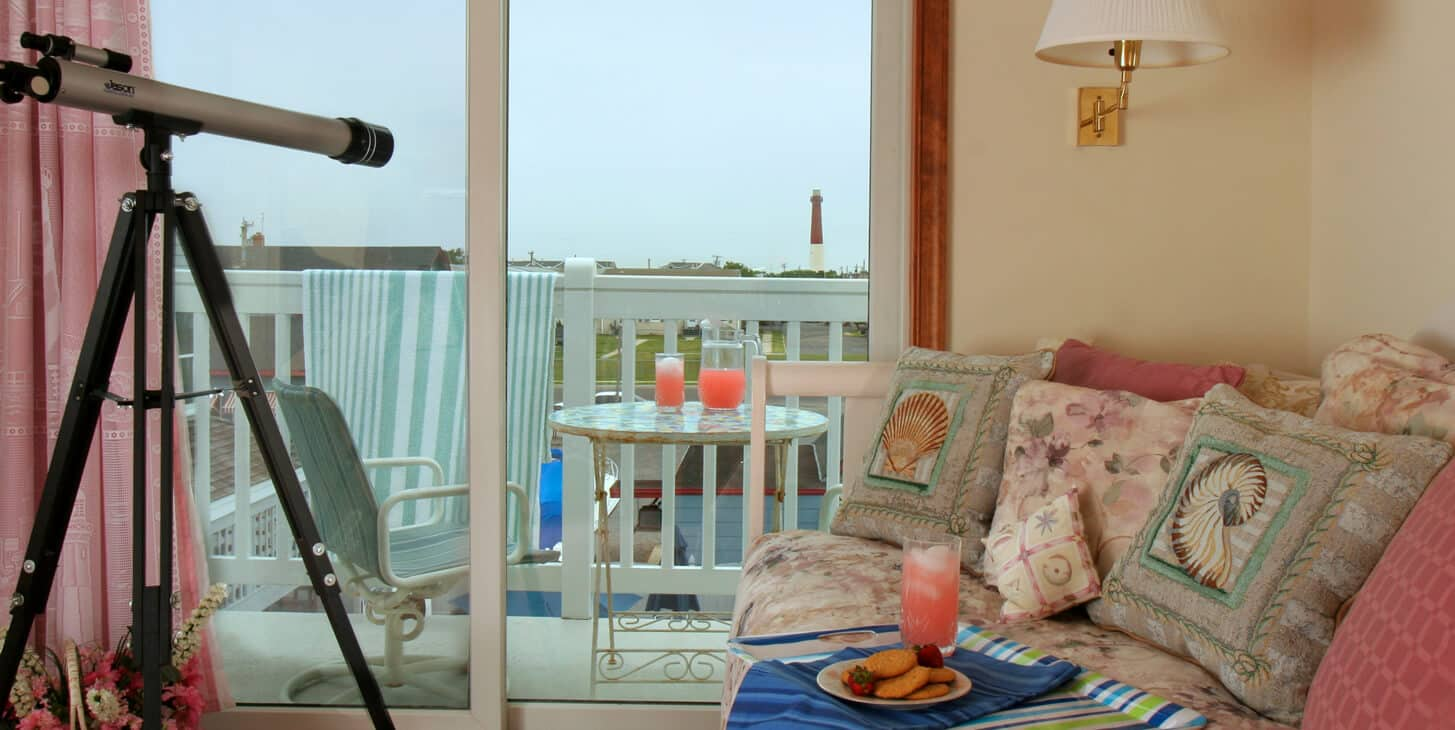 Inside room with telescope, punch on table. Looking onto patio, more punch plus view of lighthouse.