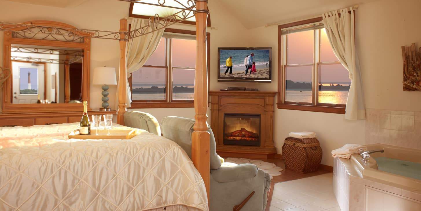 Suite showing king four poster bed, two recliner chairs and large Jacuzzi with windows overlooking sunset on the bay.