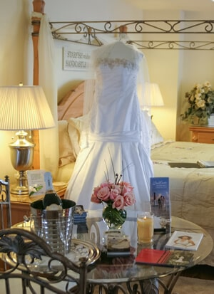 Suite showing bridal set up with gowns hanging from four poster bed and glass table with champagne
