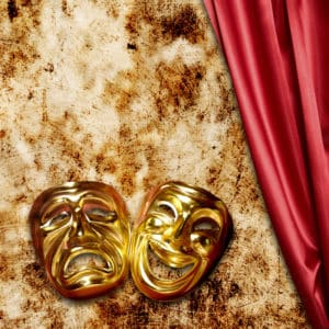 Gold theater masks next to a red curtain
