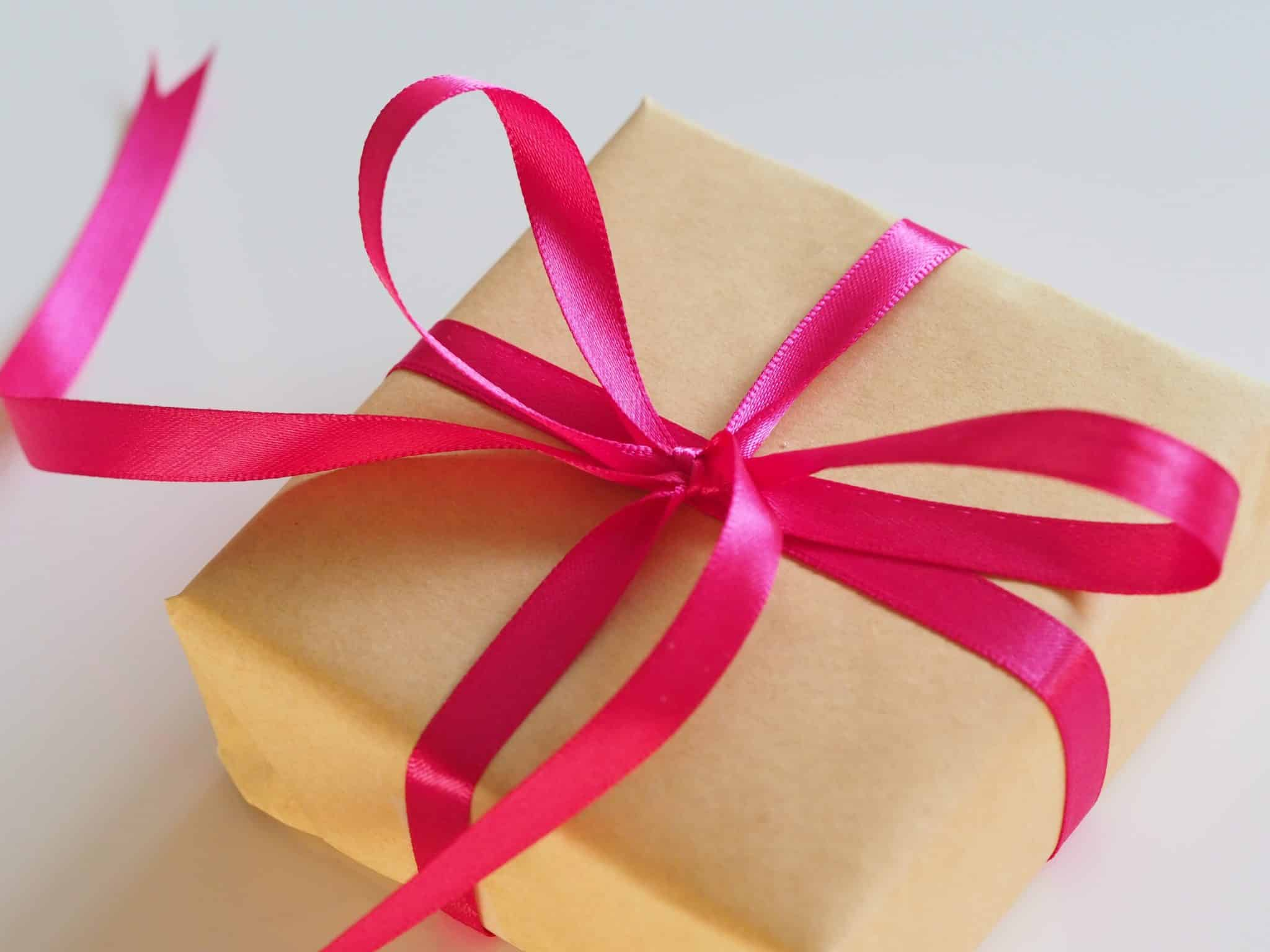 Package wrapped with brown paper and a pink bow